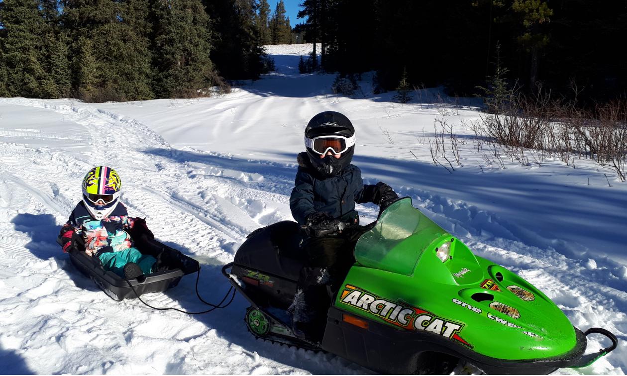 A boy riding a green snowmobile pulls a girl on a toboggan behind him.