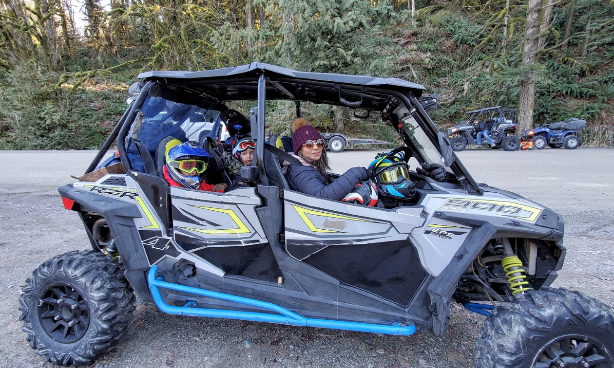 A woman and two children sit in a 2018 Polaris RZR S4 900.