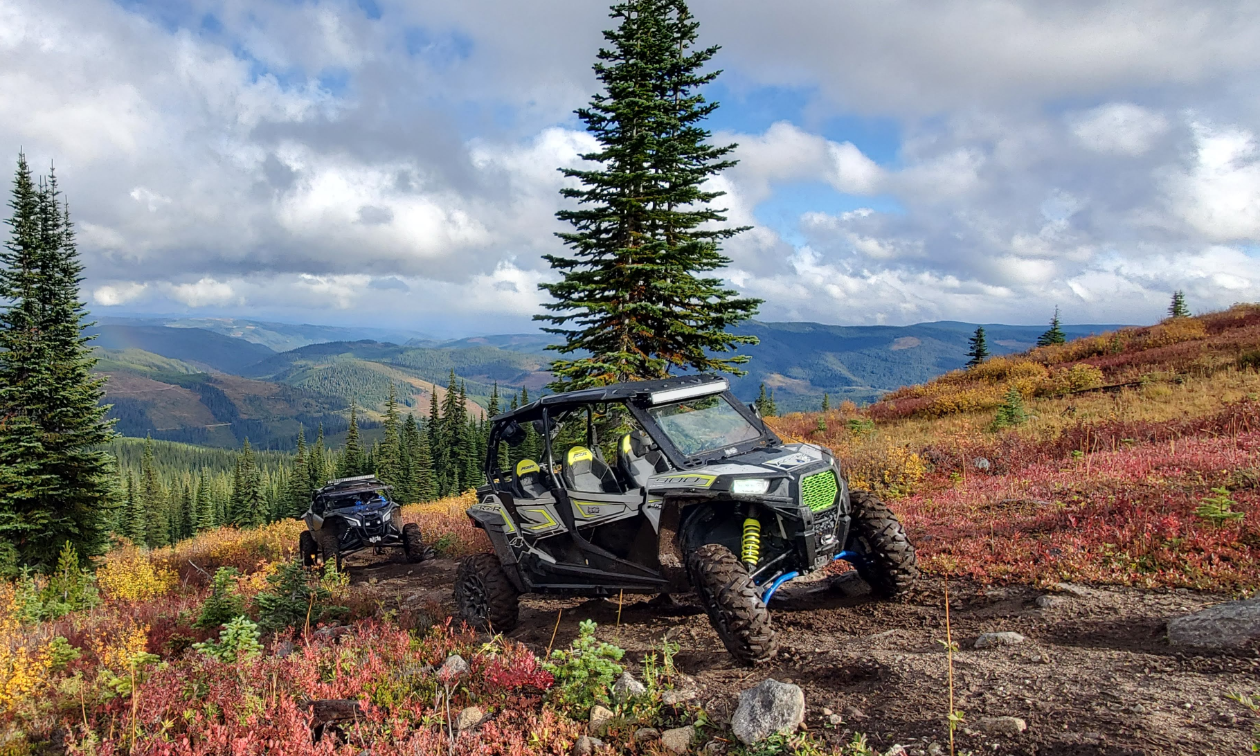 A 2018 Polaris RZR S4 900 is parked on a trail high in the mountains on a cloudy day.