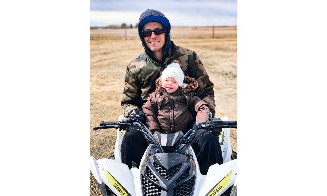 Dan Militere rides a Yamaha ATV with his small daughter, Tess.