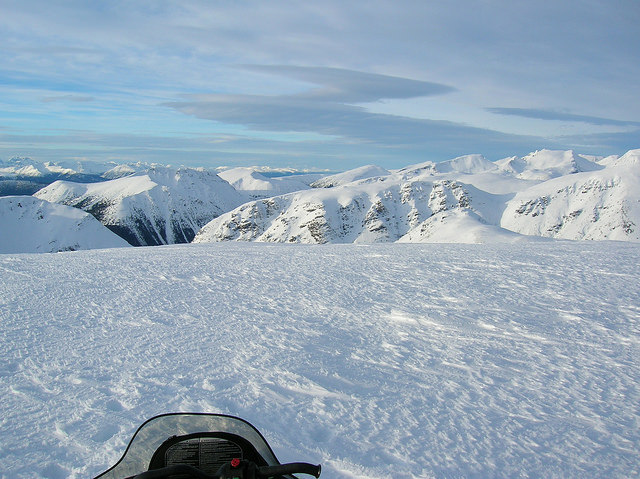 The windshield of a snowmobile is show in the forground and a stunning view of the Telkwa Range is off in the distance.