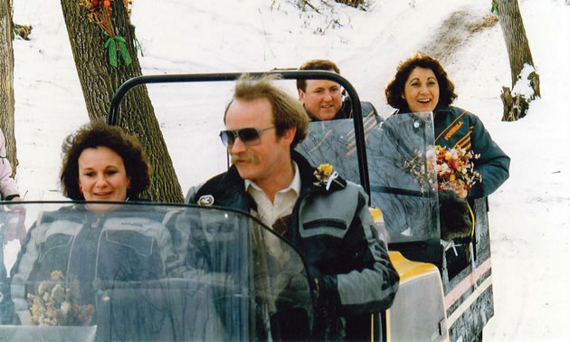 Photo of two people driving a two seater snowmobile and towing a couple behind in a cutter on their way to a wedding.