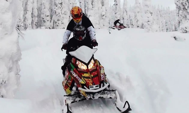 A mother and her son on a flashy red Polaris sled.