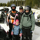 A grandmother, mother and her two daughters standing together dressed in snowmobile gear and they are surrounded by snowmobiles.
