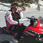Photo of a girl siting on a red snowmobile with snow and trees in the background