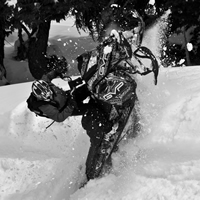 A black and white photo of a guy hitting a wind lip on a sled.