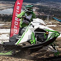 A man on a white and green Arctic Cat riding up a hillclimb.