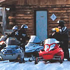 A group of snowmobilers rest in from of Red Rock Lake Shelter.