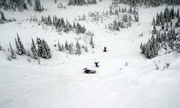 A man waves from the bottom of a snowy hill in around Valemount, BC.