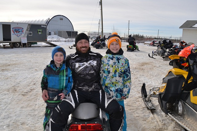 A man with two children sitting on a snowmobile.