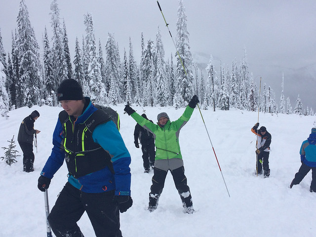 A group of people on the mountain practicing their avalanche skills training.