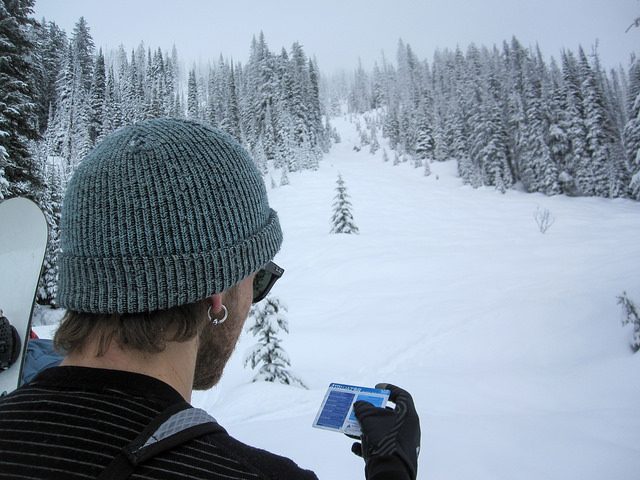 AST 1 student Clayton Zacharias using the Avaluator developed by Avalanche Canada to identify avalanche risks before crossing underneath a path.