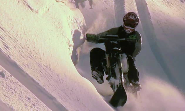 A man riding a snow bike across a steep sidehill.