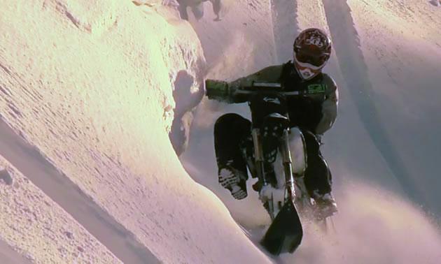 A man riding a snow bike across a steep sidehill.