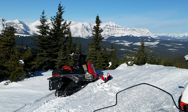 A snowmobile sitting on an overlook of the Great Divide.