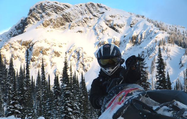 Snowmobiler up close with big mountains in the background.