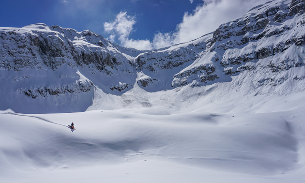 A snowmobiler on a bench below massive peaks.