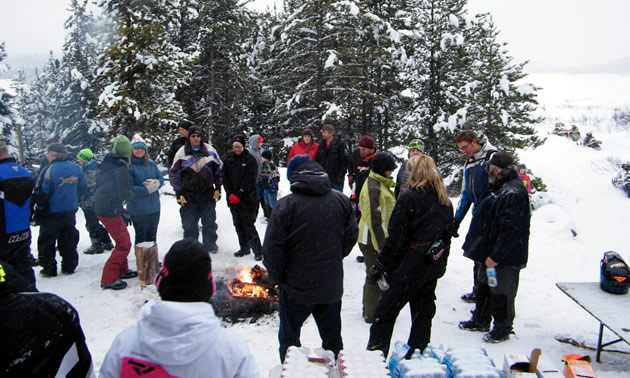 A group of snowmobilers gathered around a fire.
