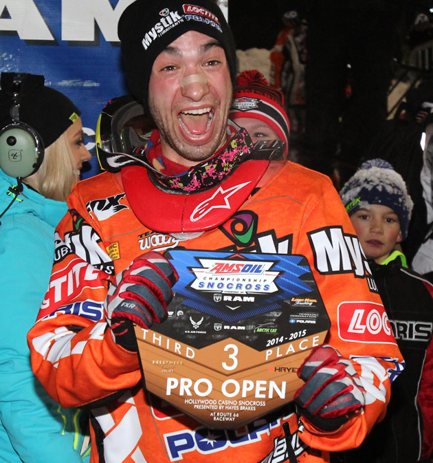 Kyle Pallin snocross racer with a big smile on his face holding a trophy.