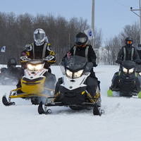 A group of women on snowmobiles out on the prairie.