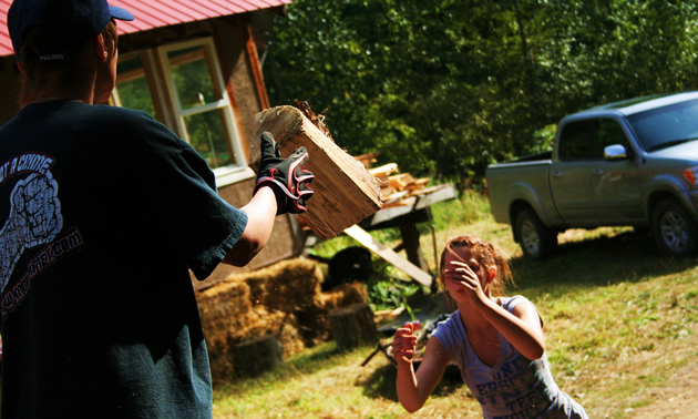 Photo of a young brown haired girl throwing a piece of wood up to a person in a black shirt and ball cap who is standing on the back of a truck.