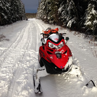 A red sled sitting at the side of a snowmobile trail.