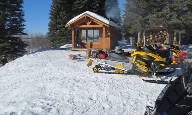 Two snowmobiles parked in front of a little cabin.