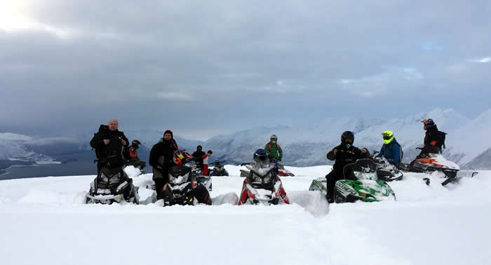 A group of snowmobilers stopped at the top of a mountain while breaking trail.