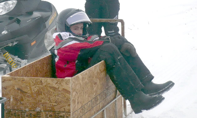 a young boy sits in a box with his snow gear on.