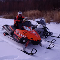 A man sitting on an orange M1000 snowmobile.