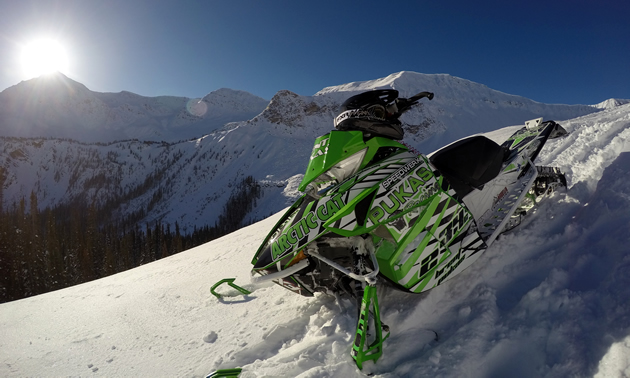 A green Arctic Cat sitting on top of a mountain with the sun in the background.