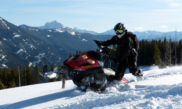 A snowmobiler on top of the mountain with mountains in the background.