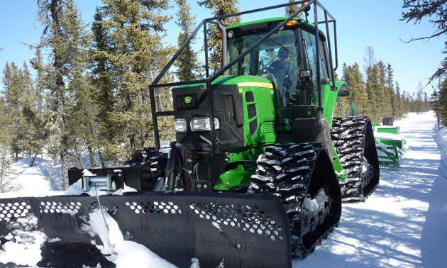 A John Deere tractor with a track kit for grooming snowmobile trails.