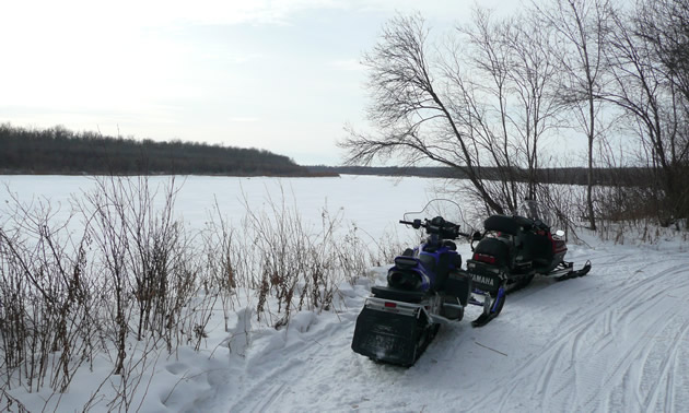 Snowmobiles parked beside a snow covered lake.