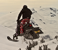 A guy soaring though the air on a sled.