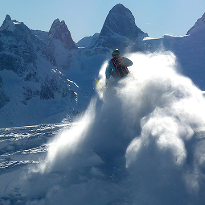 Snow billowing behind a snowmobiler who was jumping and the Bugaboo spires in the distance.