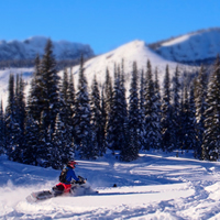 A snowmobiler riding in the mountains
