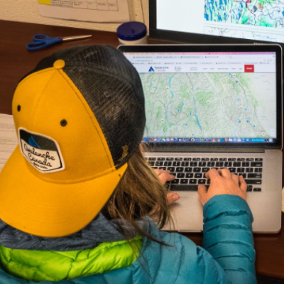 A woman wearing a backwards Avalanche Canada hat sits at a computer.