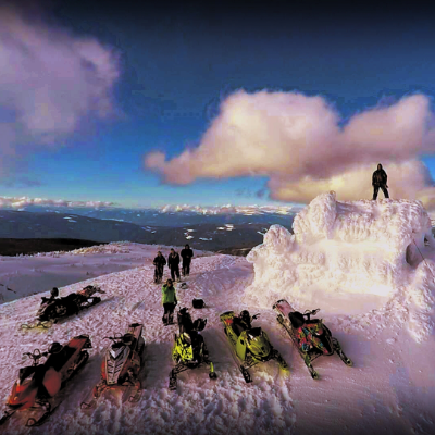 A man stands on the top of an ice sculpture igloo built on the top of a mountain with friends and their snowmobiles in front of the monument.