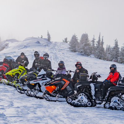 A row of snowmobile riders pose for a photo on a snowy hill.