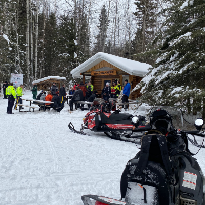 Snowmobilers gather around a cabin in the snow in Whitecourt, Alberta.