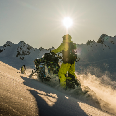 A snowmobile glides up a mountain as the sun casts shadows in the distance.
