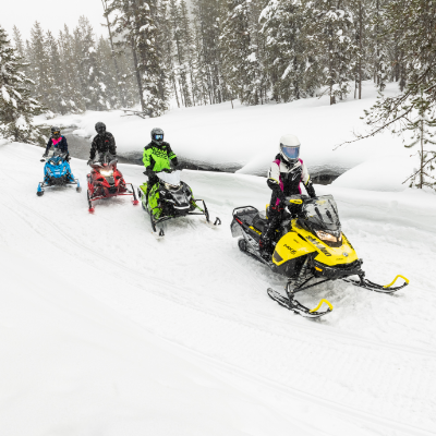 Snowmobilers ride down a snowy trail.