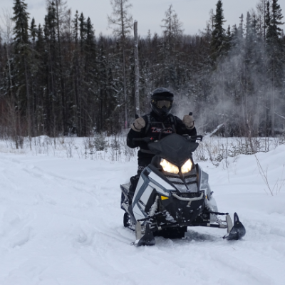 A snowmobiler dressed in black on a black snowmobile rides along a trail in the snow.