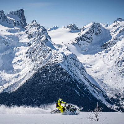 A snowmobile shreds through snow in front of towering mountains.