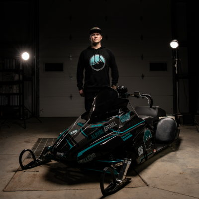 Brennan Boxall stands behind his black snowmobile, a 2014 Wahl Bros Champ.