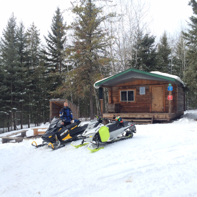 Chris Rourke poses on his snowmobile in front of a warm-up shelter