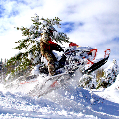 A snowmobiler gets air off a jump near a tree covered in snow.