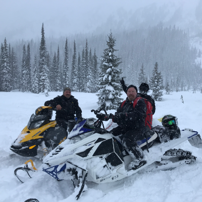 Three snowmobilers pose in a meadow as snow falls around them.