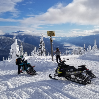 Two snowmobilers park their snowmobiles for a picture on Frisby Ridge with Revelstoke in the background.